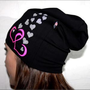Musta trikoopipo pinkeillä ja glittersydämillä nuoren naisen päässä